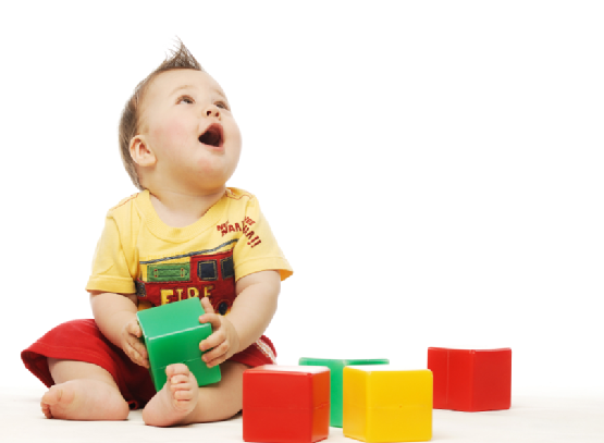 Baby in yellow shirt playing with blocks looking up surprised