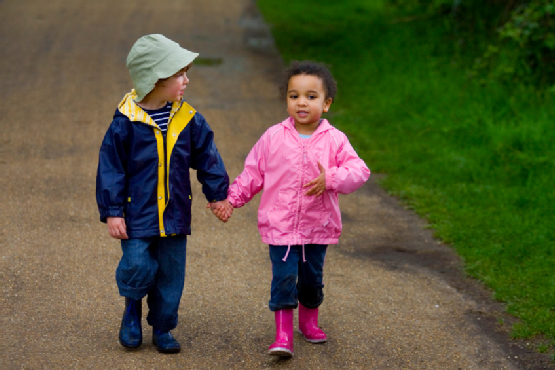 Two Children Holding Hands Walking Through A Park