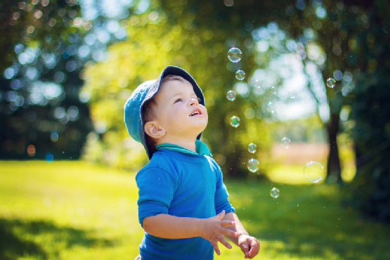 Chid looking at soap bubbles